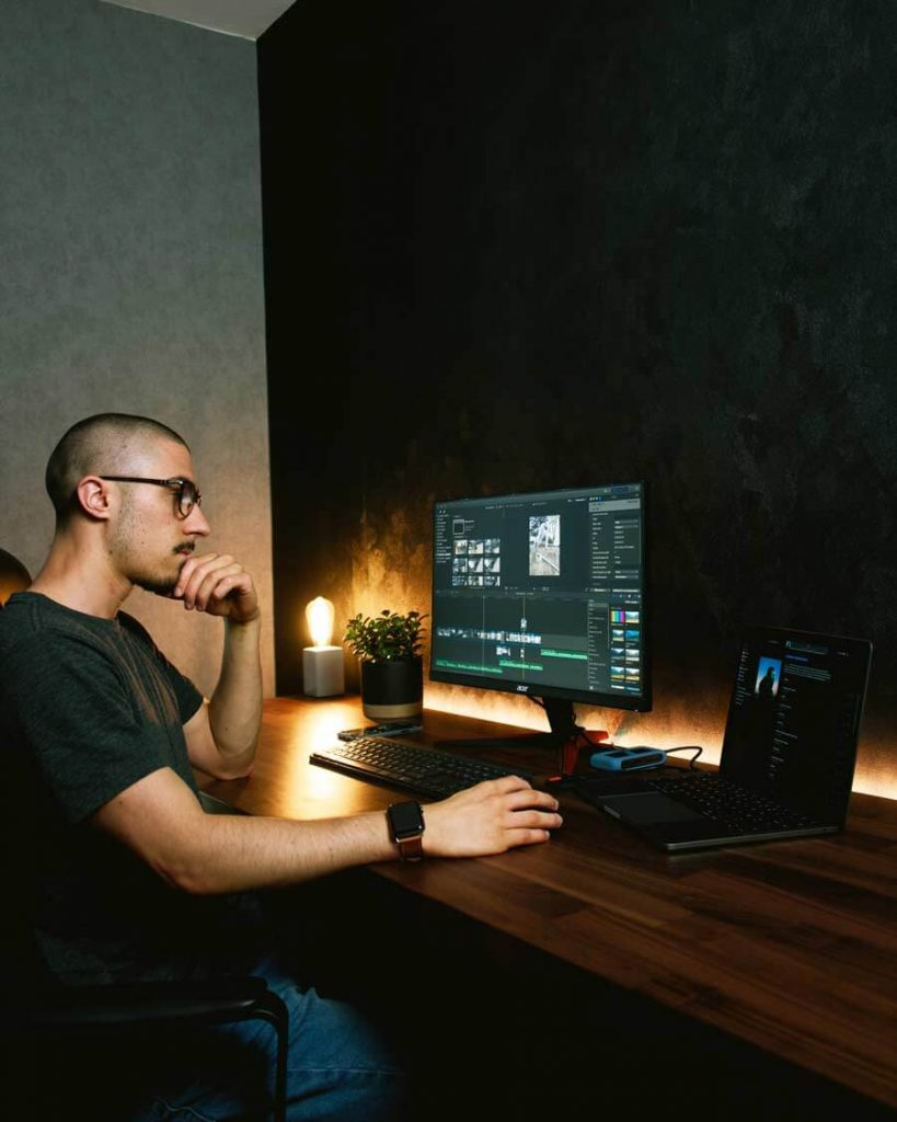 a boy is looking at a monitor in dark room